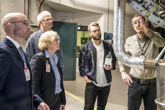 Håkan Schmidt, GKN visar RM12-motorn för fr v Håkan Johansson, Försvarsmaktens Hållbarhetssektion, Ingela Bolin Holmberg, FMV, Torbjörn Hillerström, och Fredrik Lundgren med ett biobränsleprov i handen, båda GKN.