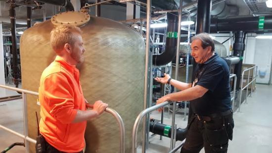 Robert, som jobbar tätt tillsammans med personalen uppe i själva badanläggningen, visar Andreas Lutmark, simlärare, hur vattenreningssystemet fungerar.