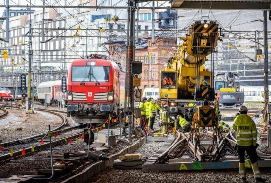 Med Vossloh Nordics spårgående Kirow-kran kan trafiken köra som normalt förbi arbetsplatsen. Här passerar Snälltåget förbi precis utanför Stockholms centralstation.