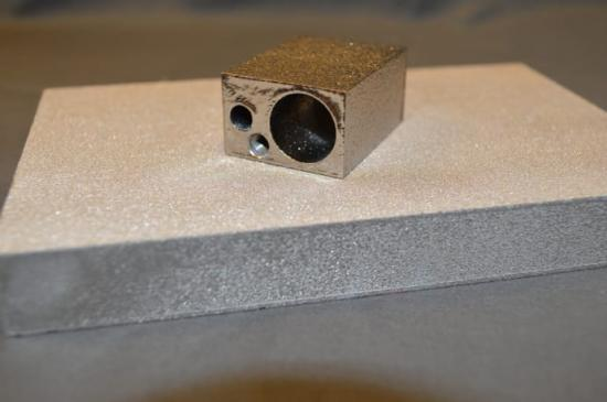 Bilden visar skillnaden mellan ett 3D-printat föremål (det övre) som har genomgått efterbearbetning och ett föremål (det undre) som inte efterbearbetats.